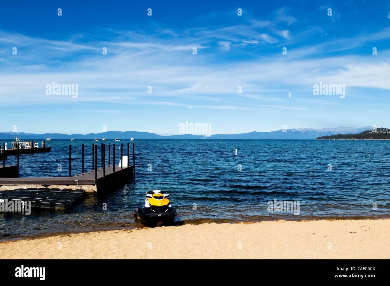 South Lake Tahoe With Blue Sky White Clouds Docks And Ski Jet On Sand Beach Stock Photo