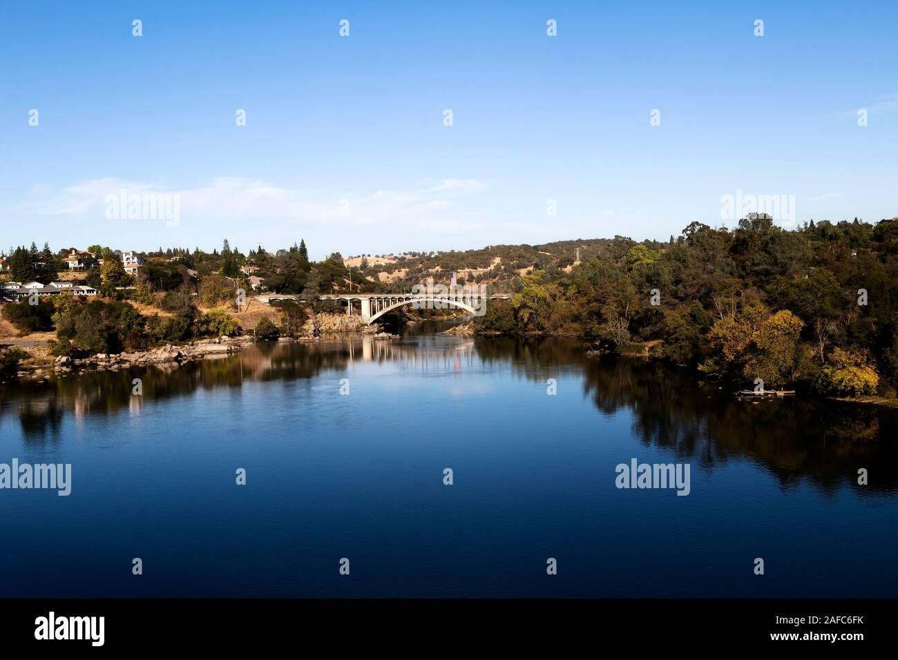 Blue Water And Sky Lake Natoma And Rainbow Bridge Folsom California With Trees Reflected In Water Stock Photo