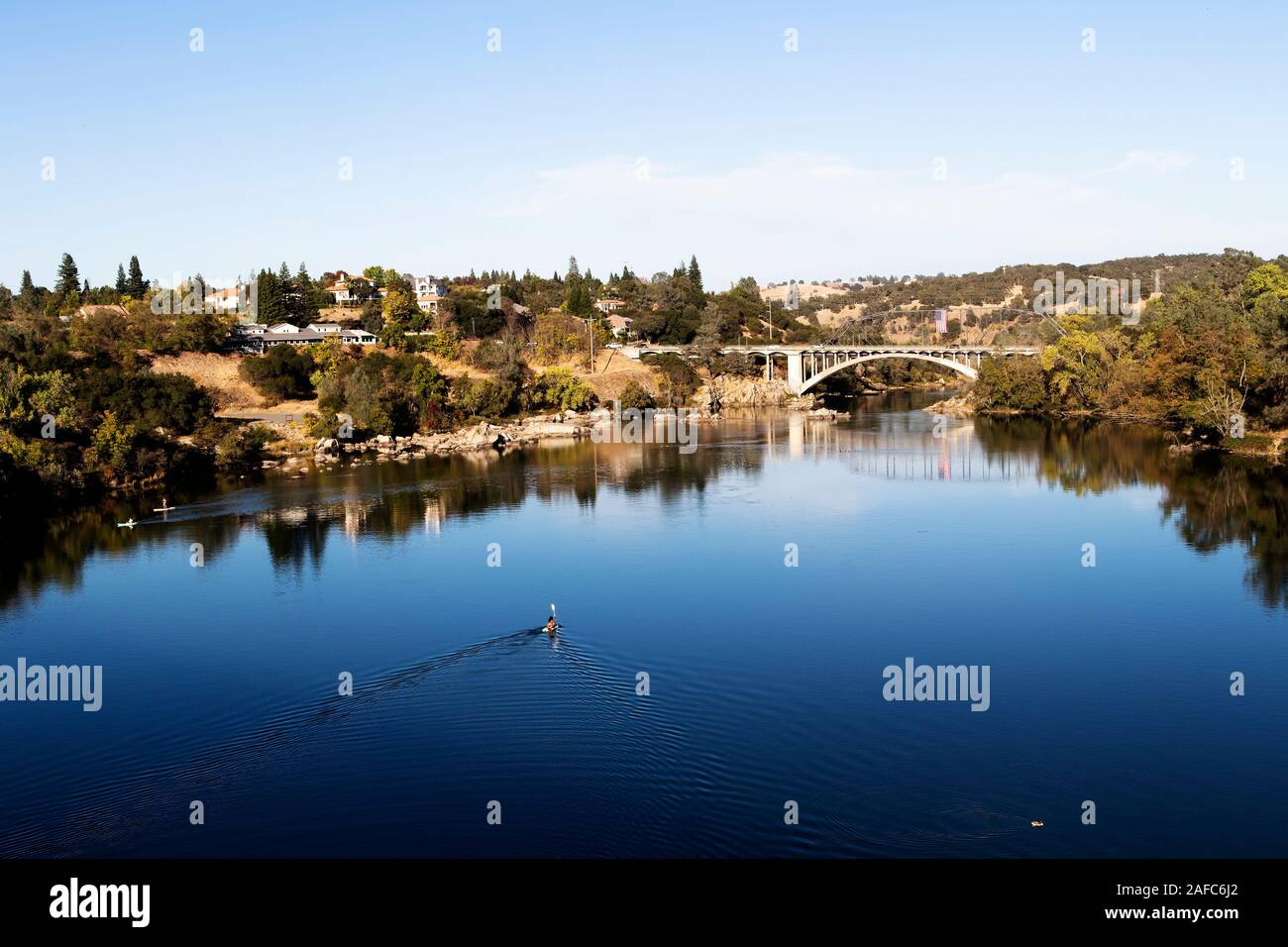 Blue Water And Sky Lake Natoma And Rainbow Bridge Folsom California With Trees Reflected In Water People Paddling Stock Photo