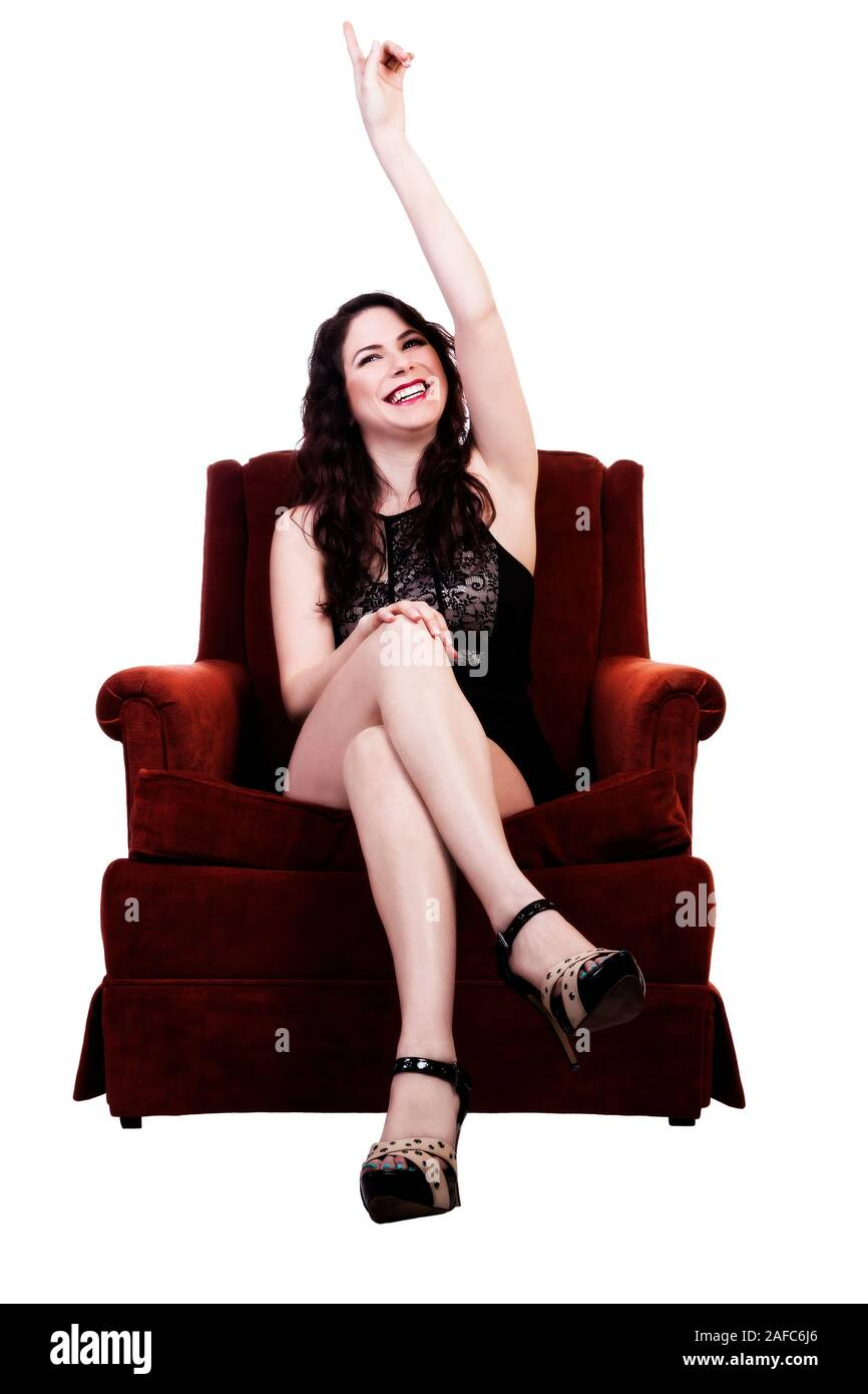 Smiling Young Caucasian Woman In Black Dress Sitting In Red Chair Pointing Up Stock Photo
