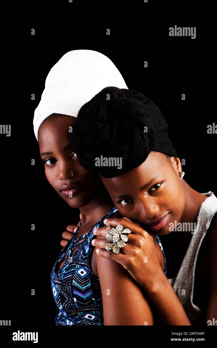 Two Attractive Young African American Women Wearing Black And White Headscarfs On Dark Background Stock Photo