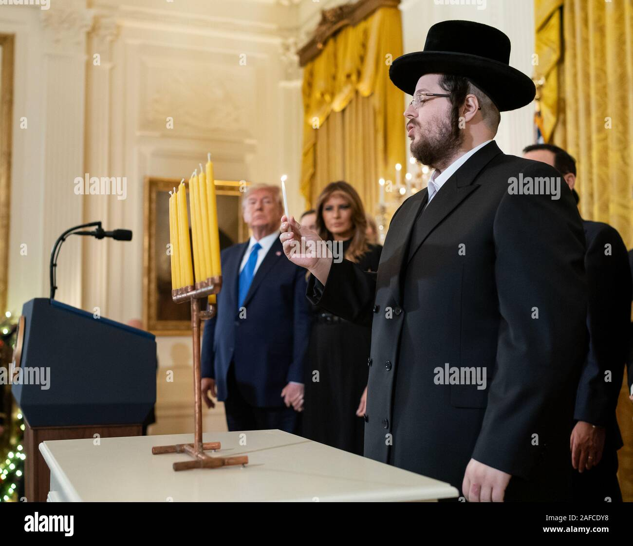 Washington, United States Of America. 11th Dec, 2019. President Donald J. Trump and First Lady Melania Trump look on as Rabbi Moshe Moskowitz lights the Menorah during a Hanukkah Reception Wednesday, Dec. 11, 2019, in the East Room of the White House People: President Donald J. Trump, Rabbi Moshe Moskowitz Credit: Storms Media Group/Alamy Live News Stock Photo
