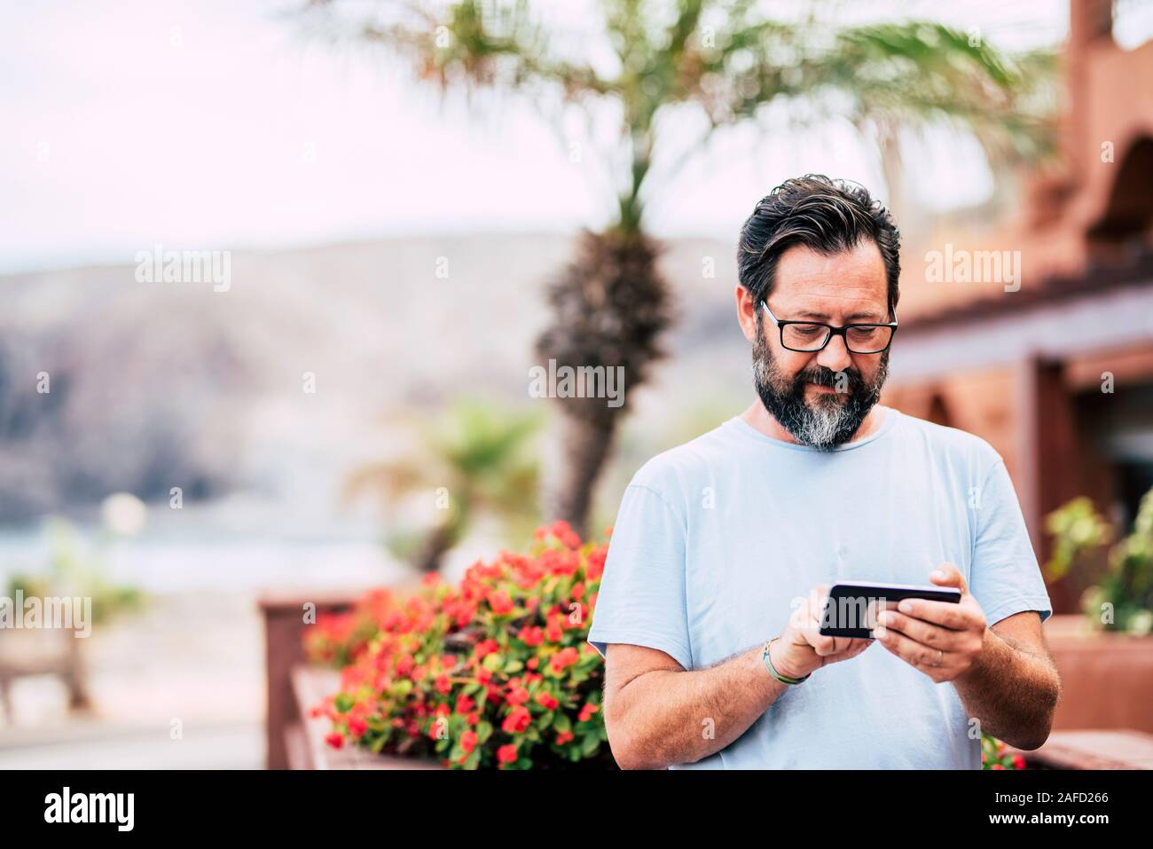 Man type on a modern cellular phone device in outdoor leisure activity with technology - portrait of aged adult with defocused background Stock Photo