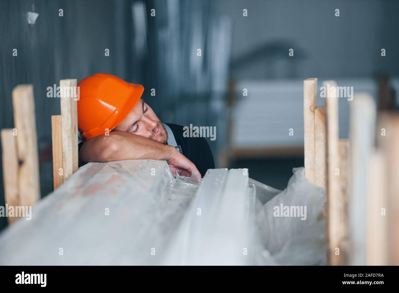 Sleeping on a job. Taking a break. Industrial worker indoors in factory. Young technician with orange hard hat Stock Photo