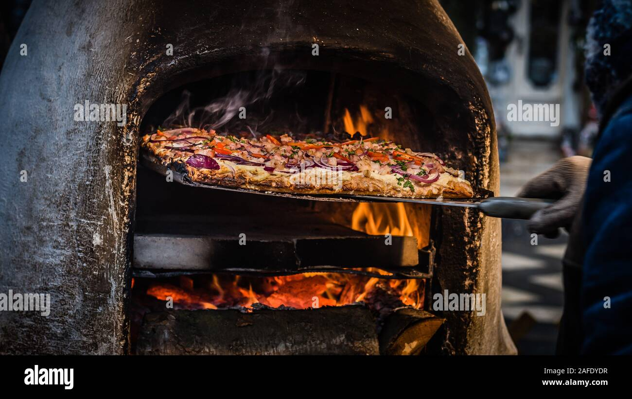 Man removing freshly made pizza street food from wood fired oven in Budapest Stock Photo