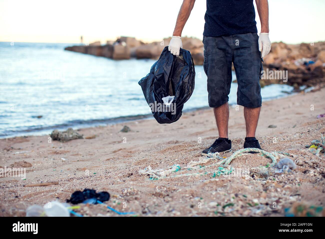Man in dark shirt and shorts with white gloves and big black package collecting garbage on the beach. Environmental protection and planet pollution co Stock Photo