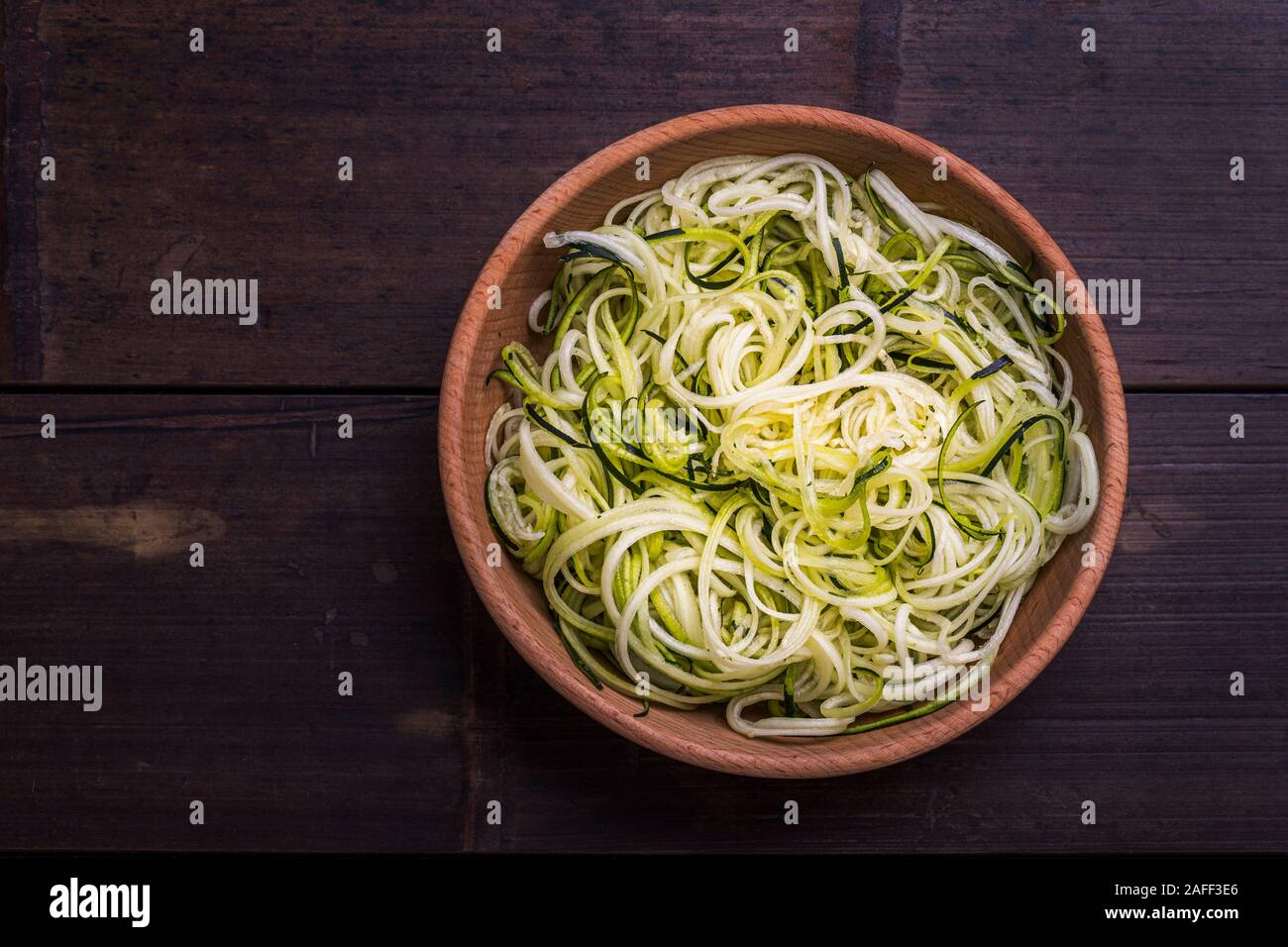 Zoodles zucchini noodles spiralized healthy  vegetable dish in a wooden bowl, on a dark bamboo table. Seen from above flat lay with copy space. Stock Photo