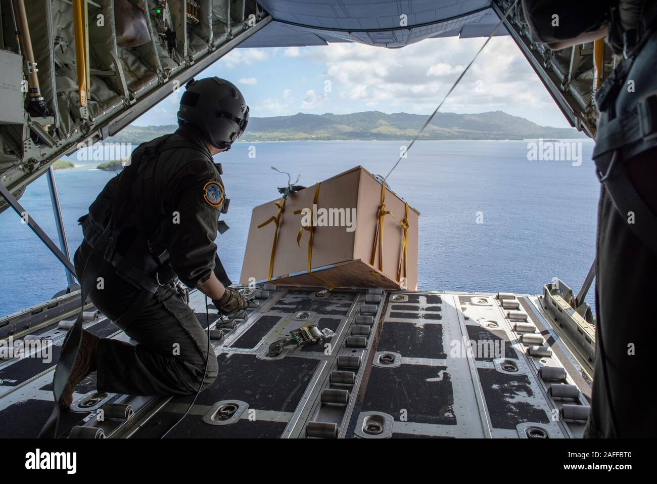 U.S. Air Force Tech. Sgt. Mario Montoya air drops a low-altitude bundle containing supplies and gifts out the back of a USAF C-130 Super Hercules aircraft December 5, 2019 over Micronesia. Over the past 68-years, the U.S. Air Force Operation Christmas Drop has been providing critical supplies to 56 Micronesian islands, impacting approximately 20,000 people across an 1.8 million square nautical miles area. Stock Photo