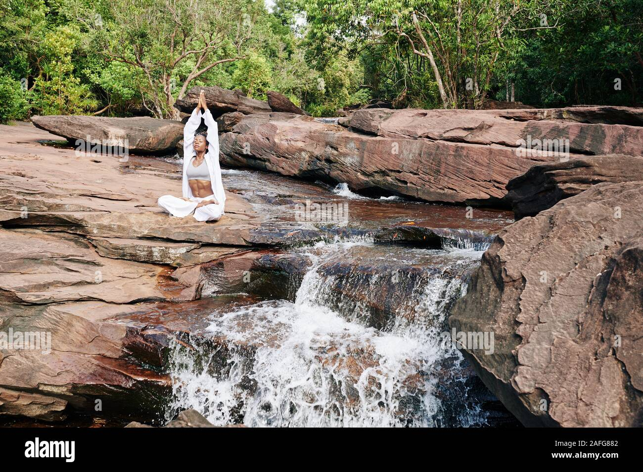Beautiful Young Woman Sitting By Waterfall And Enjoying Meditation In Nature Stock Photo Alamy
