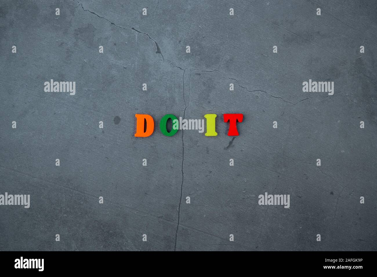 The multicolored do it word is made of wooden letters on a grey plastered wall background Stock Photo