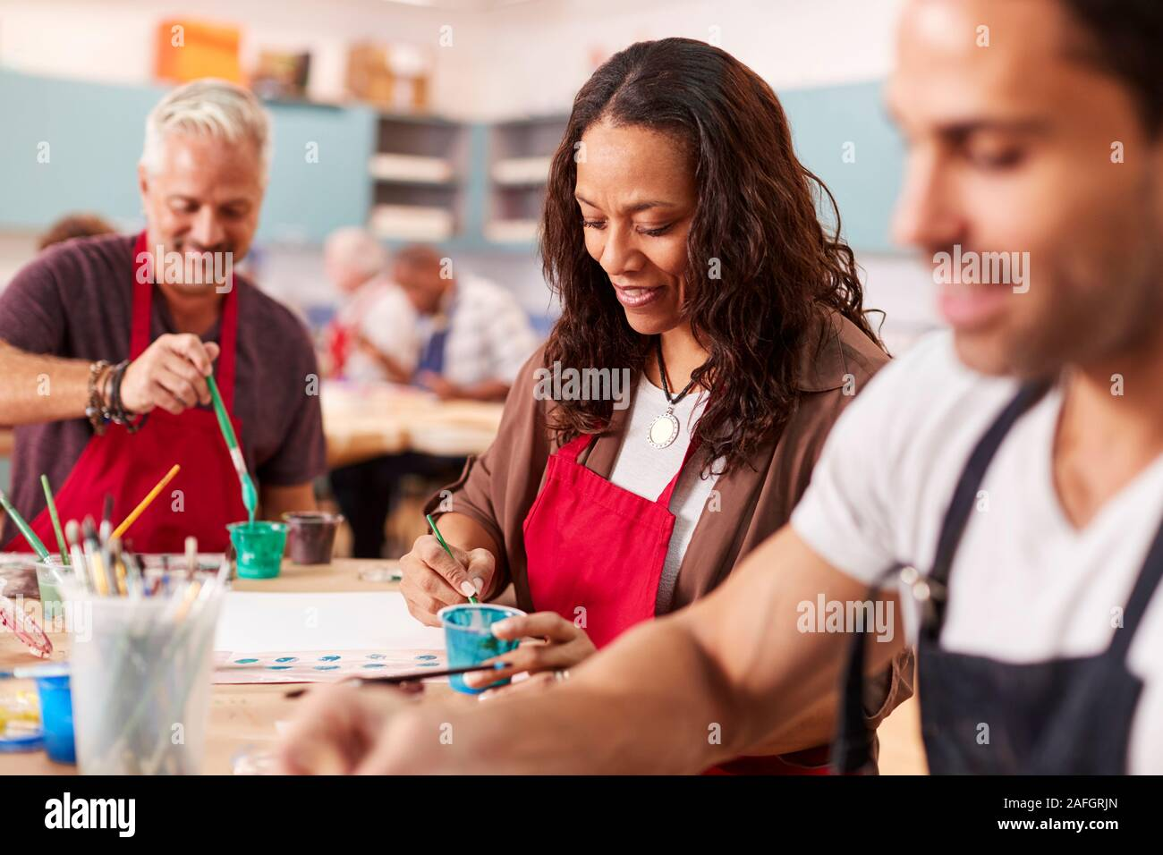 Group Of Mature Adults Attending Art Class In Community Centre Stock Photo