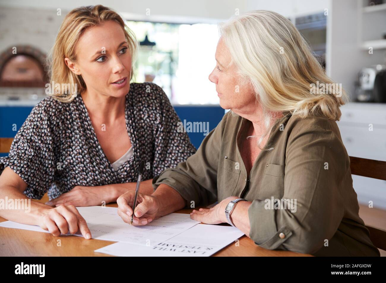 Female Friend Helping Senior Woman To Complete Last Will And Testament At Home Stock Photo