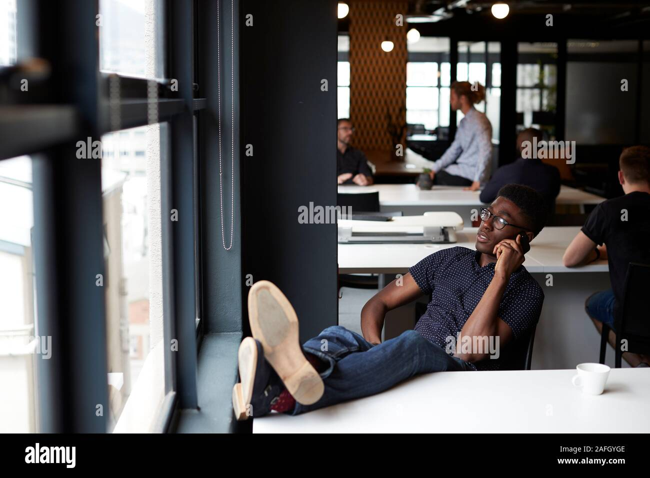 Young black male creative sitting in an office with his feet up on the desk using phone, close up Stock Photo