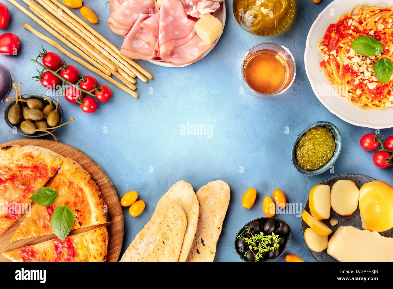 Italian food background. Pizza, pasta, cheese, hams, wine, olives, pesto, capers, shot from the top, forming a frame for copy space, a flat lay Stock Photo