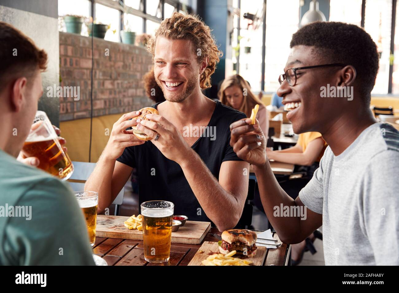 Three Young Male Friends Meeting For Drinks In Restaurant Stock Photo
