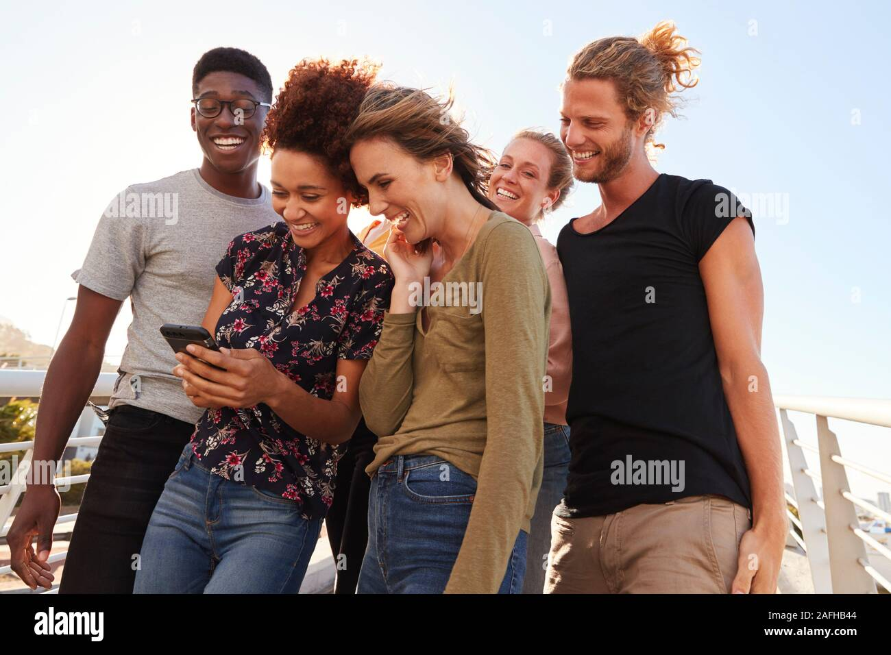 Smiling Young Friends Looking At Selfie On Outdoor Footbridge Together Stock Photo