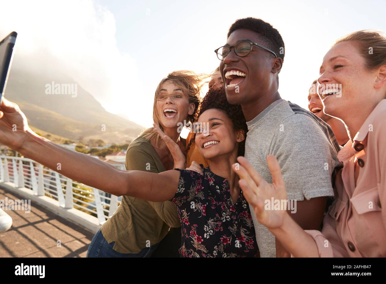 Smiling Young Friends Posing For Selfie On Outdoor Footbridge Together Stock Photo