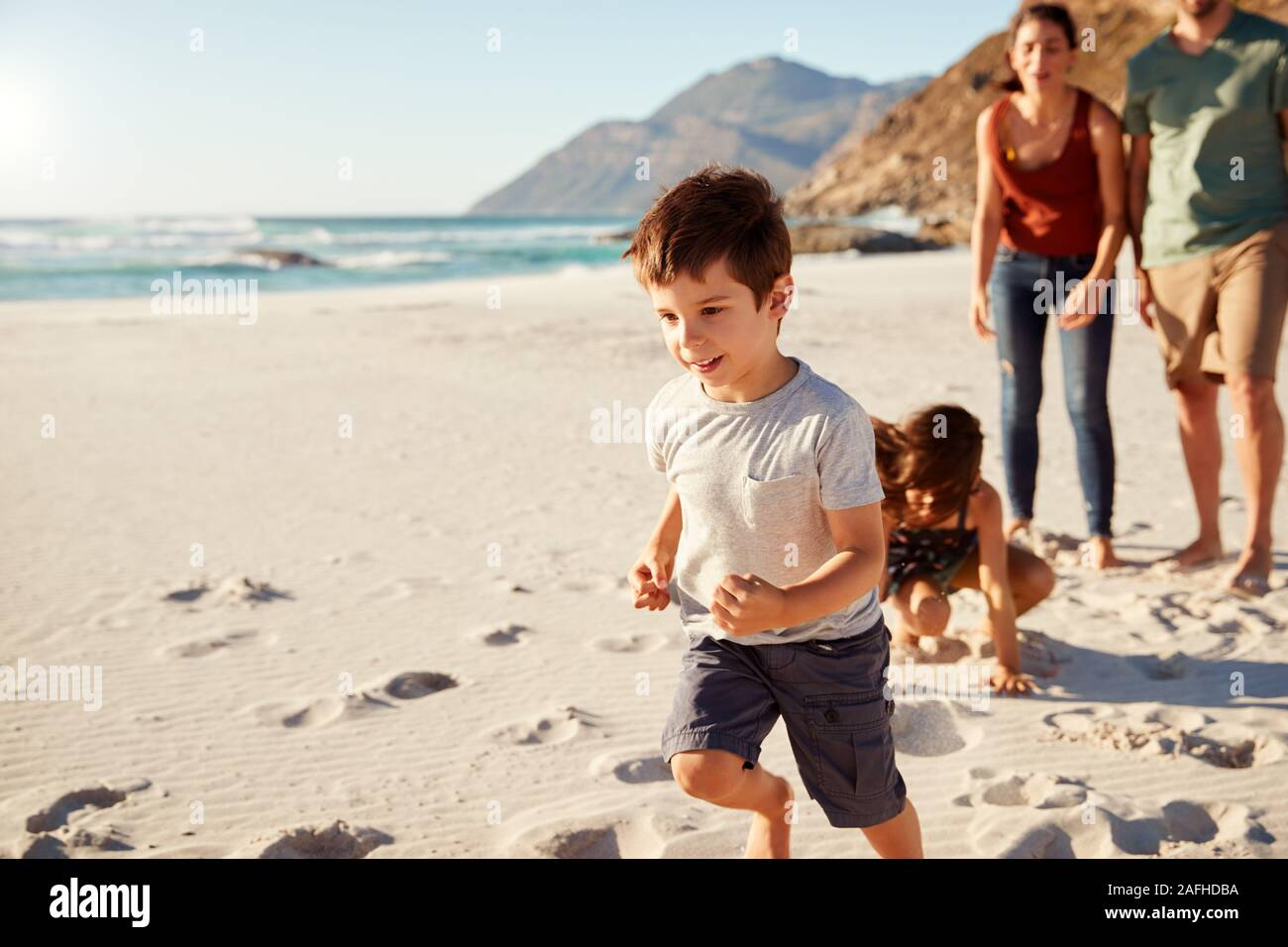 Happy young white family on holiday exploring a beach together, full length, close up Stock Photo