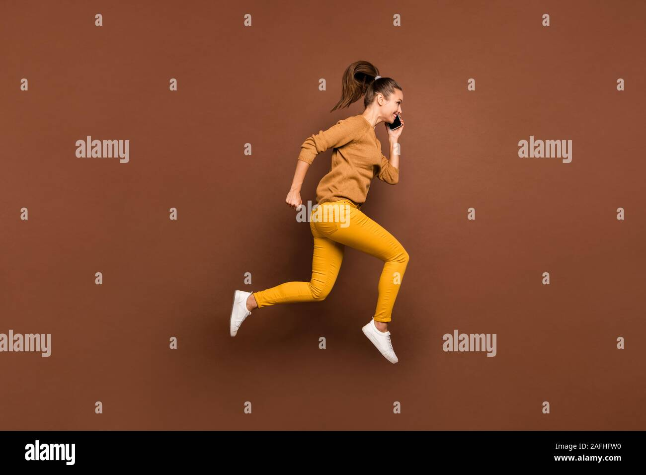 Full length body size side profile photo of young girl speaking by her phone running towards discounted shopping mall wearing trousers pants isolated Stock Photo