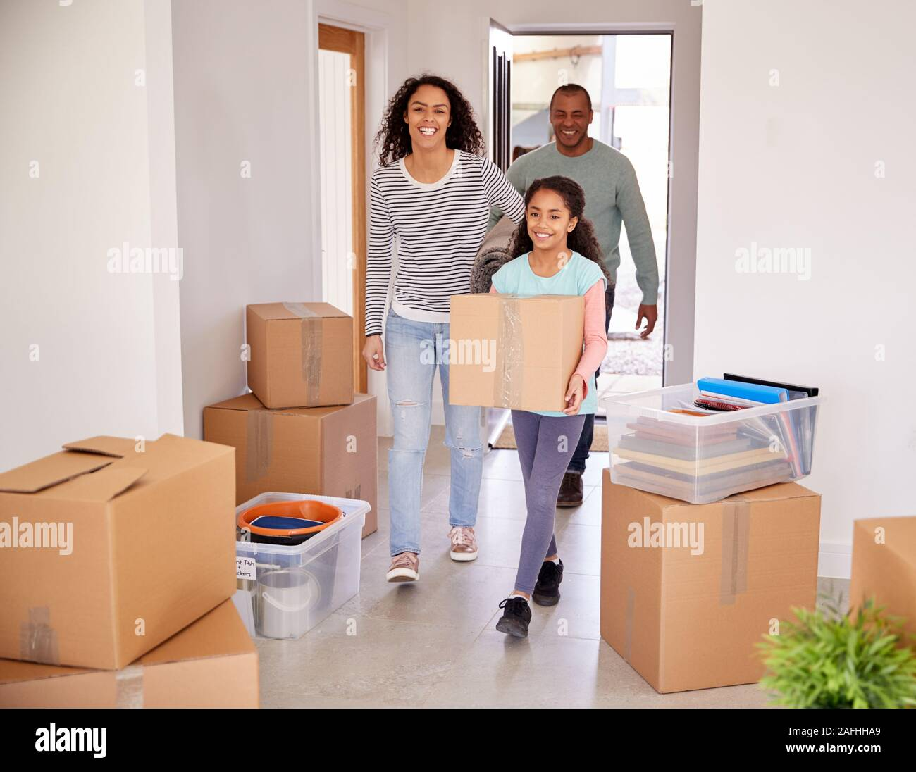 Smiling Family Carrying Boxes Into New Home On Moving Day Stock Photo