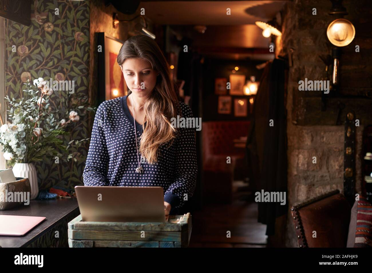 Female Receptionist Working On Laptop At Hotel Check In Stock Photo