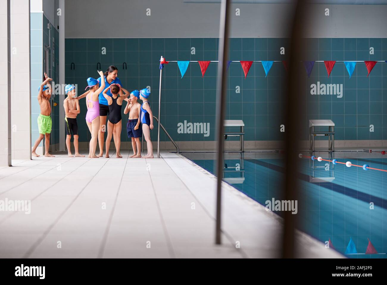 Female Coach Giving Children In Swimming Class Briefing As They Sit On Edge Of Indoor Pool Stock Photo