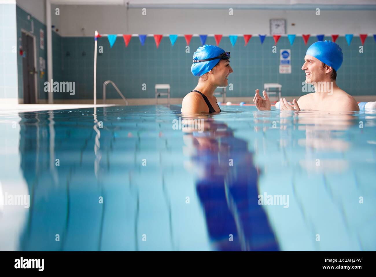 Male Swimming Teacher Giving Woman One To One Lesson In Pool Stock Photo
