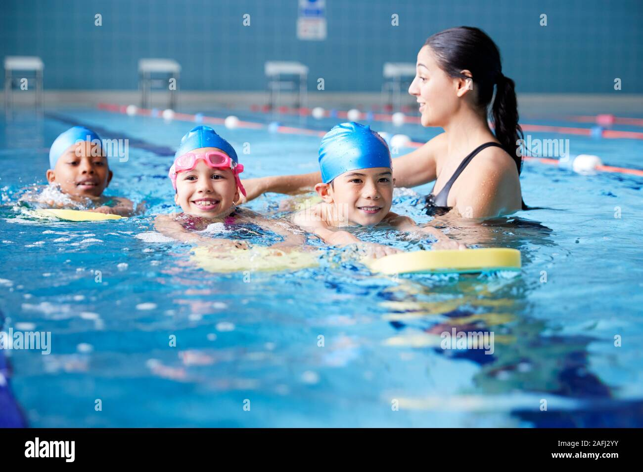 Female Coach In Water Giving Group Of Children Swimming Lesson In Indoor Pool Stock Photo