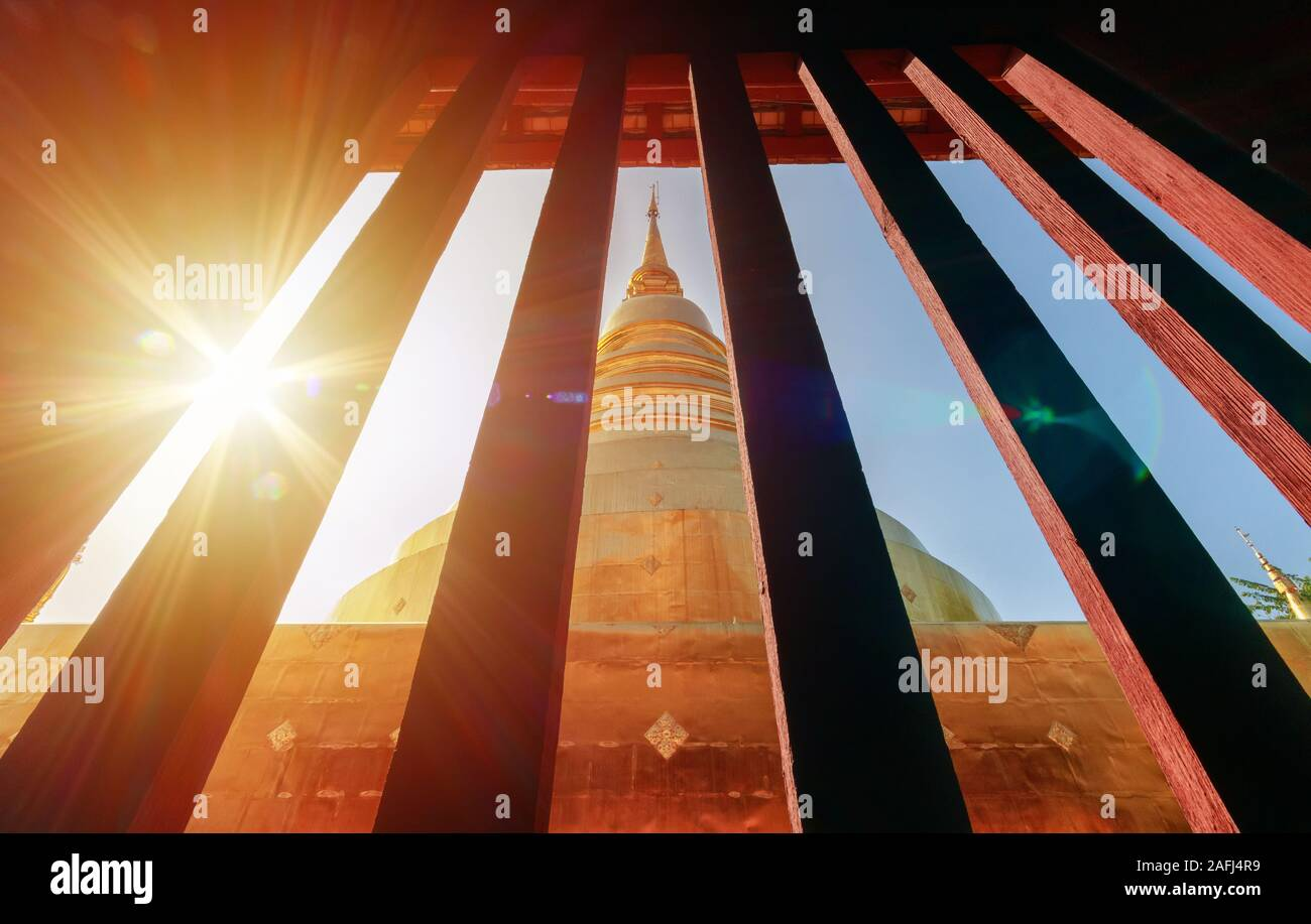 golden pagoda view from vintage window at Wat Phra Singh in Chiang Mai, Thailand with light flare in the morning. travel destination landmark Stock Photo