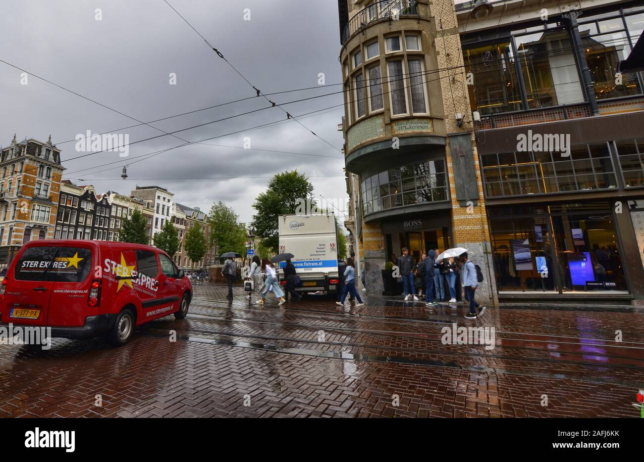 Amsterdam, Holland, August 2019. Rainy day in the old town. The silhouettes of people and things are reflected on the wet road. People cross the cross Stock Photo
