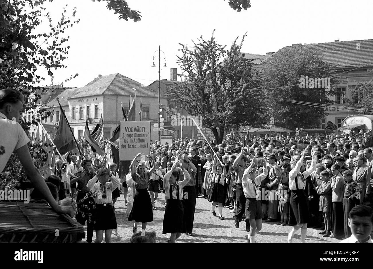 "Young Pioneers dancing with flags and poster (""Vorwaerts, Junge Pioniere beim Aufbau des Sozialismus!"", Go ahead Young Pioneers to create socialism) during a parade in Fuerstenwalde on May 1. Stock Photo"