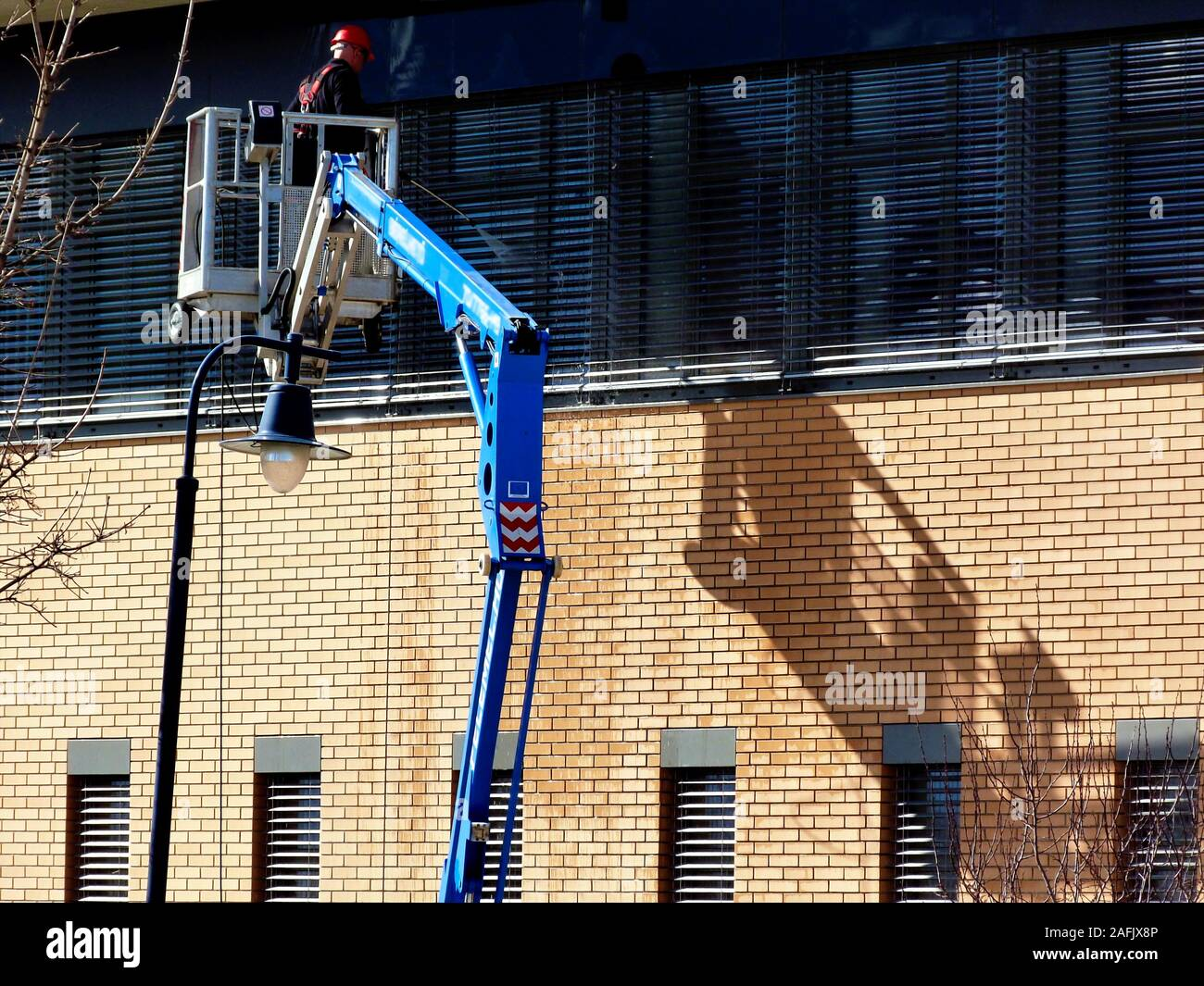 high level window cleaning. telescopic hydraulic work cage on mechanical boom. brick exterior wall. high pressure water jet. worker in red hardhat. Stock Photo