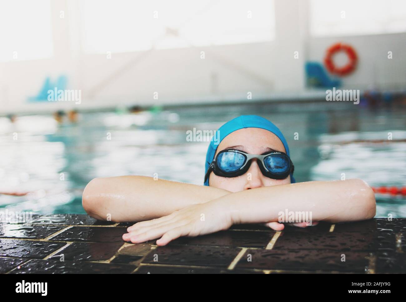 School boy swimmer in swimming blue cap and glasses on the pool, children sport Stock Photo