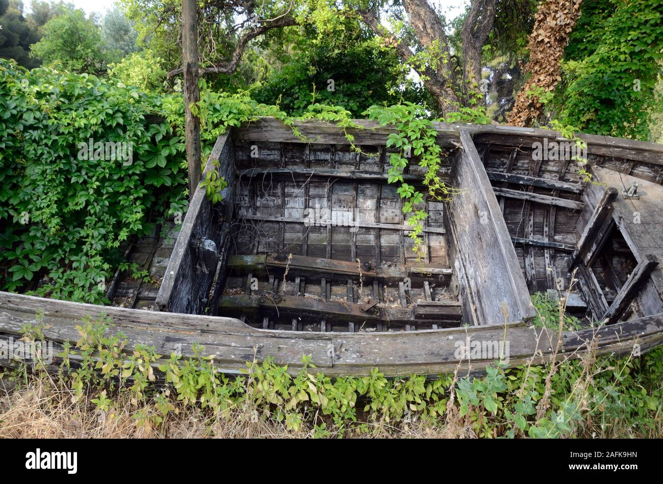Abandoned Wrecked Boat or Old Wooden Boat Covered in Overgrowth at La Seyne-sur-Mer Var Provence France Stock Photo