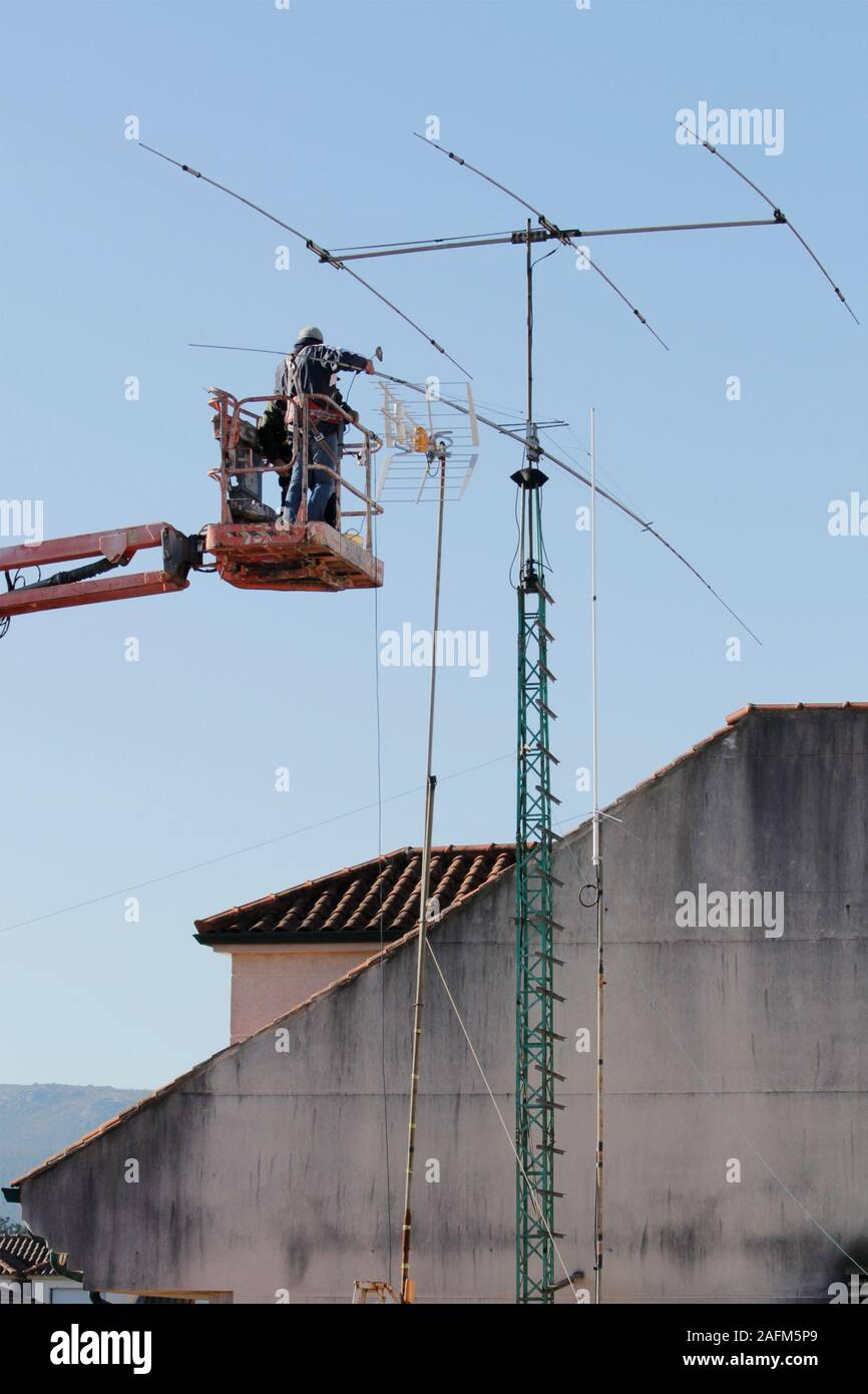 Worker on telescopic elevator repairing a antenna with blue sky on background. Communication maintenance Stock Photo