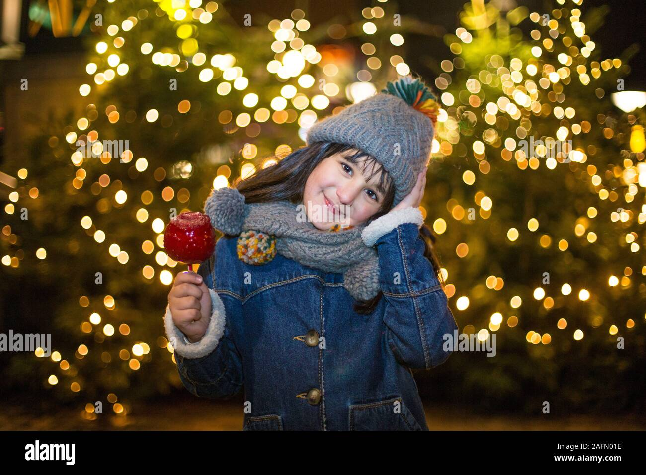 Happy girl in winter with paradise apple at Oberhausen Centro Stock Photo