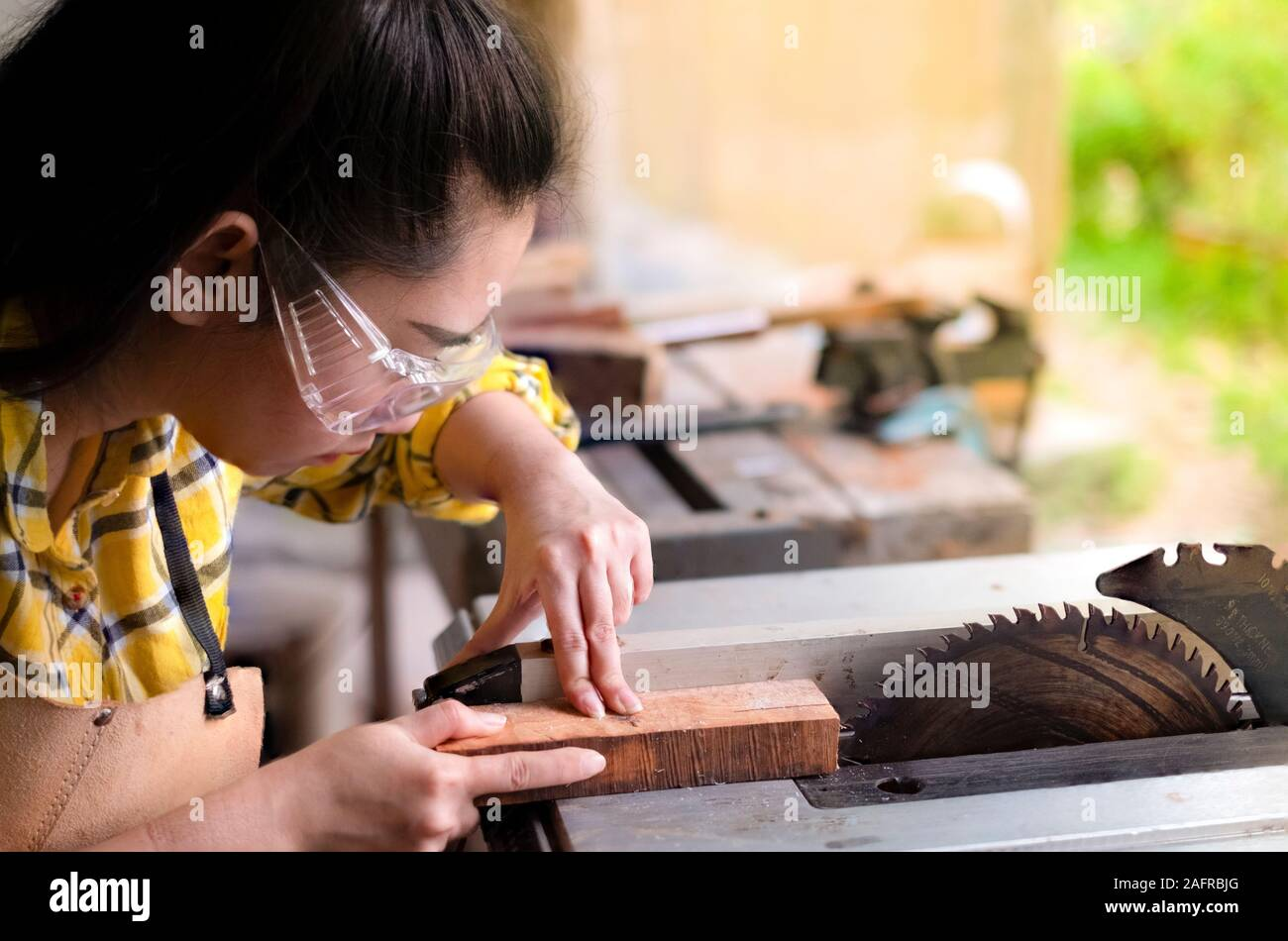 Women standing is craft working cut wood at a work bench with circular saws power tools at carpenter machine in the workshop Stock Photo