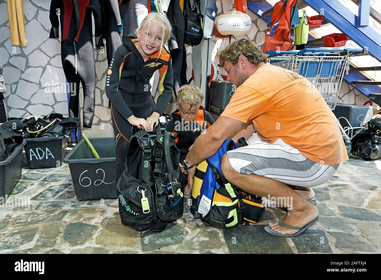 Children discover scuba diving, scuba instructor helps children to prepare diving equipment, Zakynthos island, Greece Stock Photo