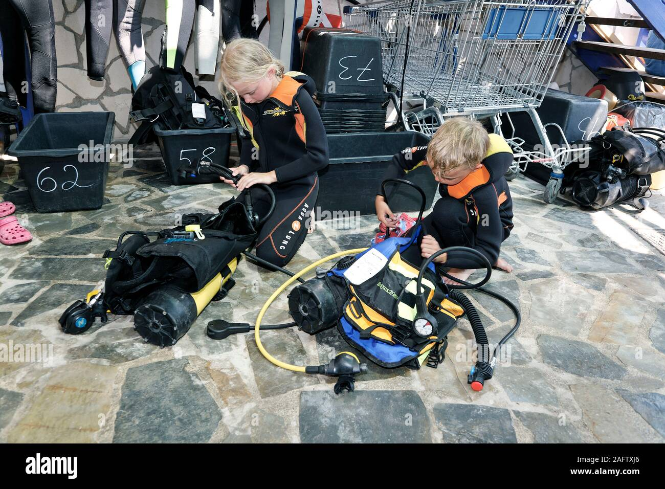 Children preparing diving equipment for discover scuba diving,  Zakynthos island, Greece Stock Photo