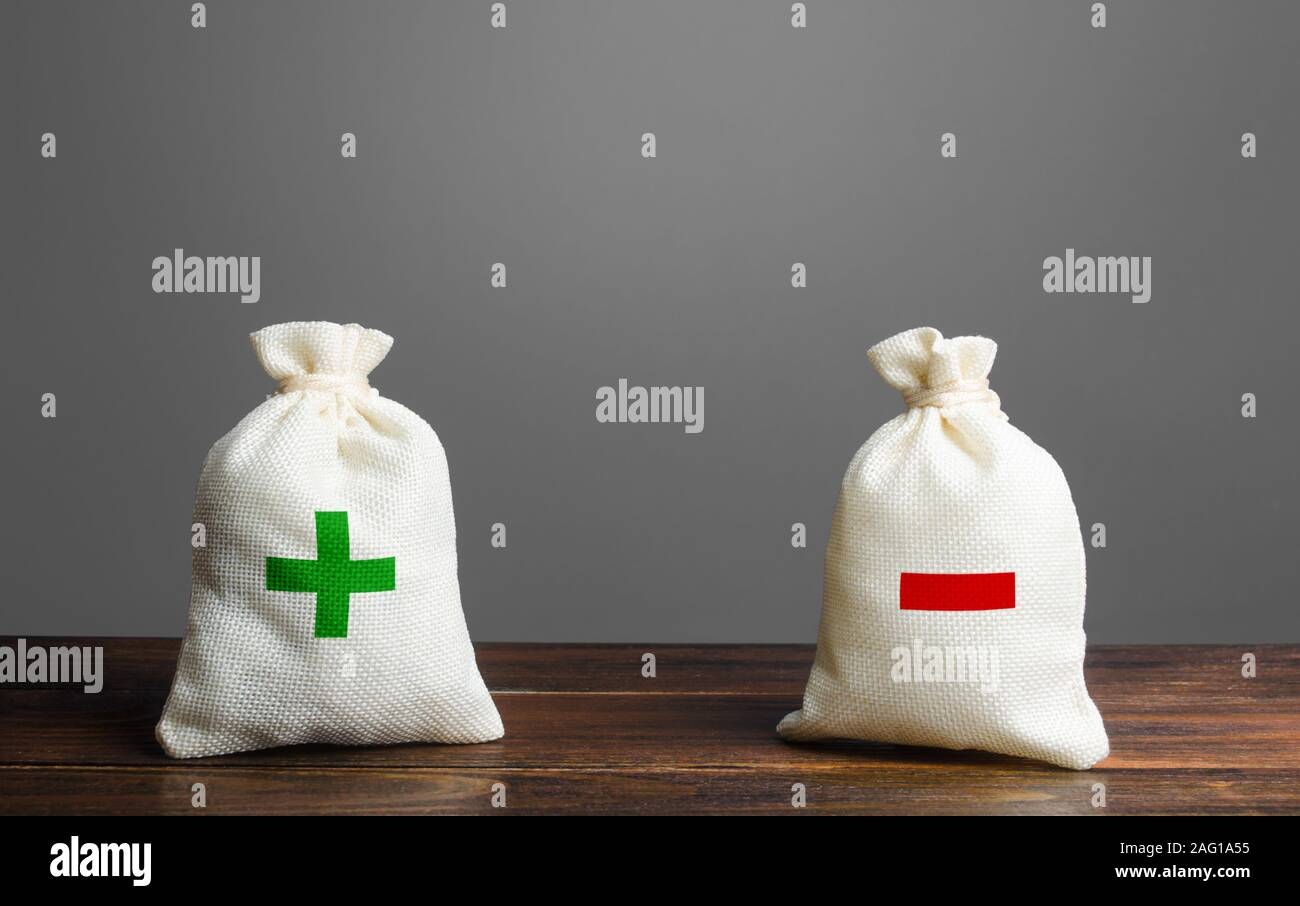 Two bags with green plus red minus. Summary and balance sheet. Income and expenses. Trade balance budgeting. Financial management, profit, losses. Ris Stock Photo