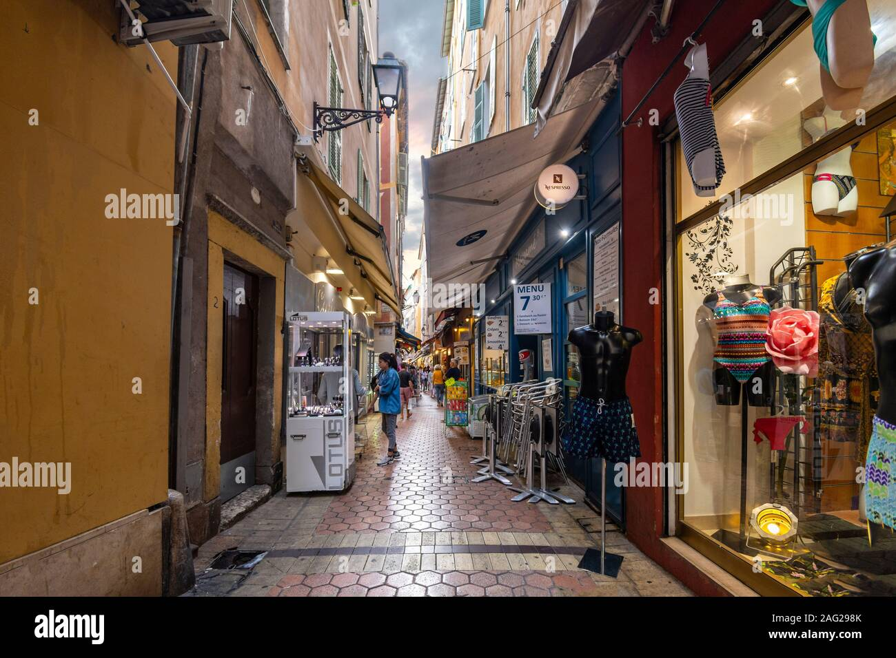 Tourists shop a very narrow alley full of cafes and shops in the Old Town of Vieux Nice, France, on the French Riviera. Stock Photo