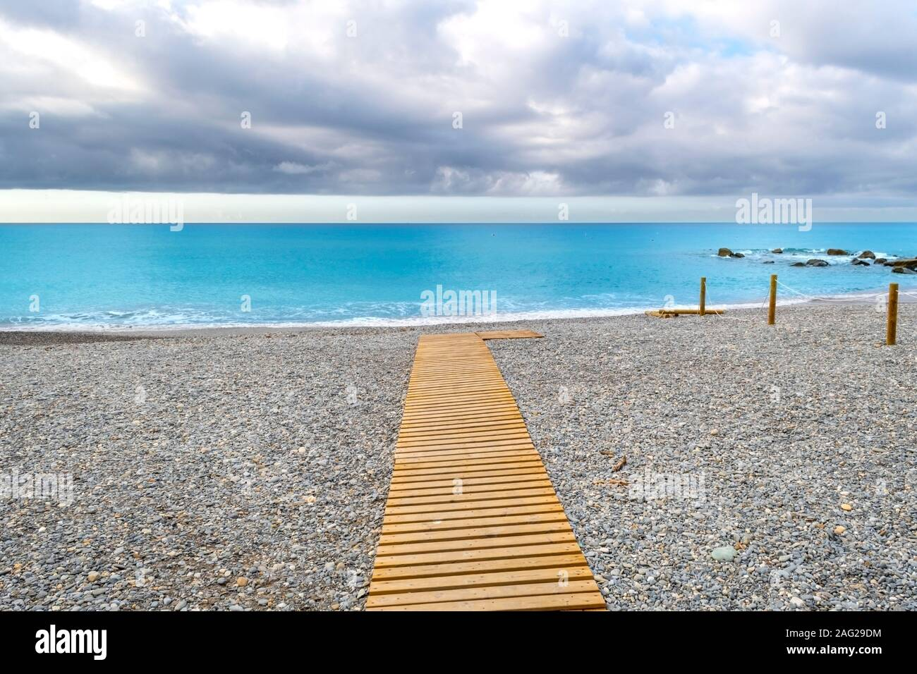 A beach pathway to the sea on an overcast morning on the Italian Riviera at Ventimiglia, Italy Stock Photo