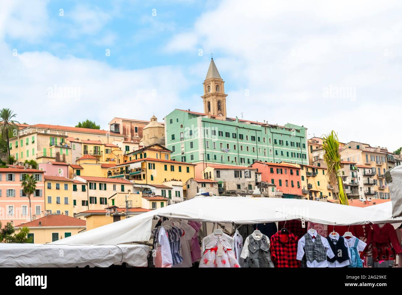 The colorful, medieval hilltop village of Ventimiglia, Italy, on the Italian Riviera rises above a clothing sale shop during the Friday outdoor market Stock Photo