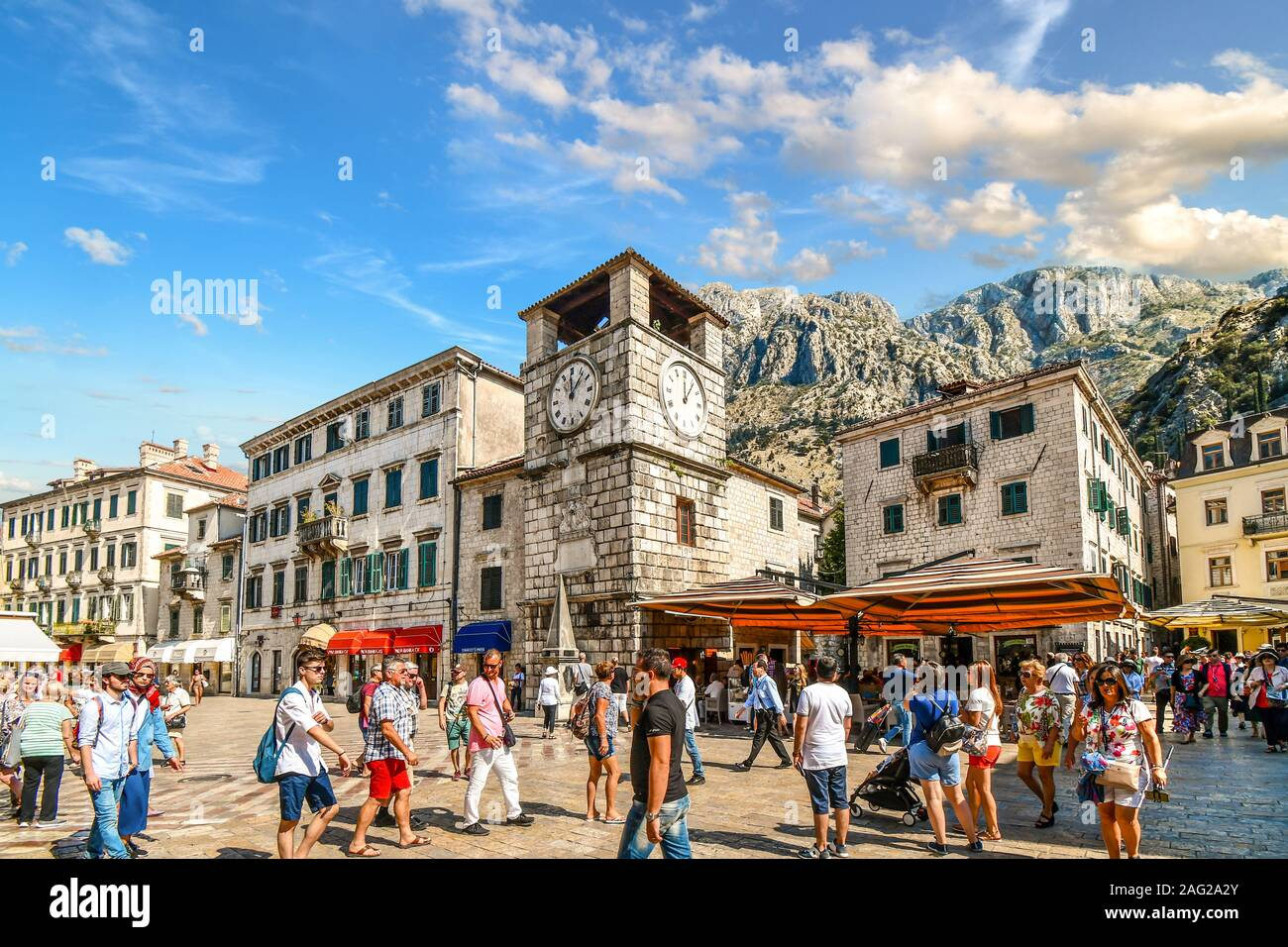 Tourists sightsee, dine at cafes and shop under the clock tower in the Square of the Arms, in the medieval walled city of Kotor, Montenegro Stock Photo