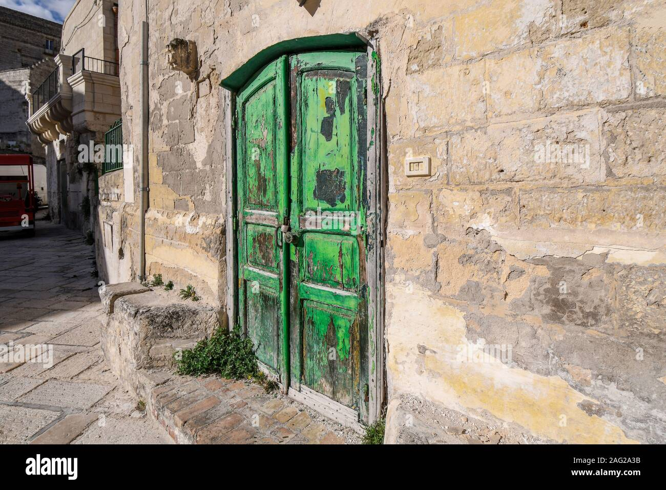 A brilliant, bright green, weathered wooden doorway into a stone building in the ancient city of Matera, Italy, in the Basilicata region. Stock Photo