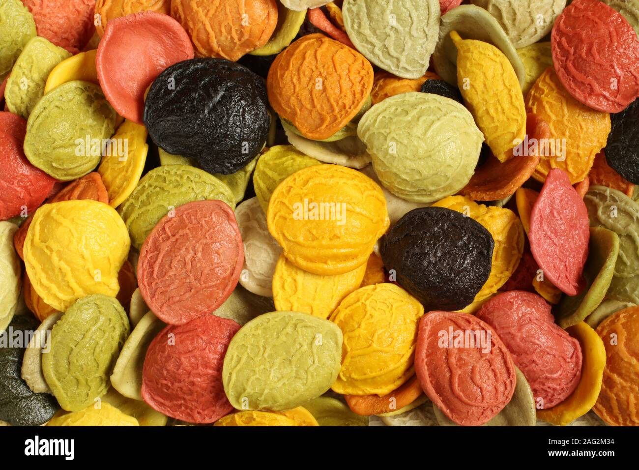 Colorful durum wheat orecchiette pasta with special ingredients: dried carrot, red beet, spinaches, basil, tomatoes, turmeric powder and squid ink. Stock Photo