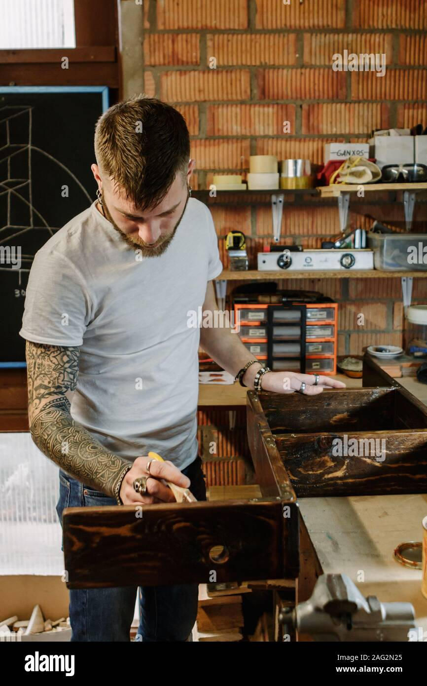 Tattooed artist applying varnish paint on a wooden furniture at craft workshop Stock Photo