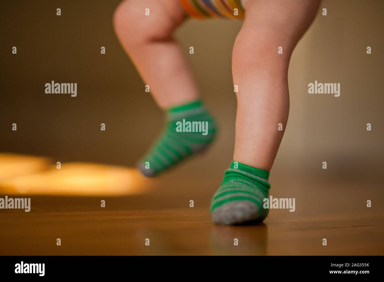 Legs Of A Baby On A Hardwood Floor While Bouncing In A Baby Jumper