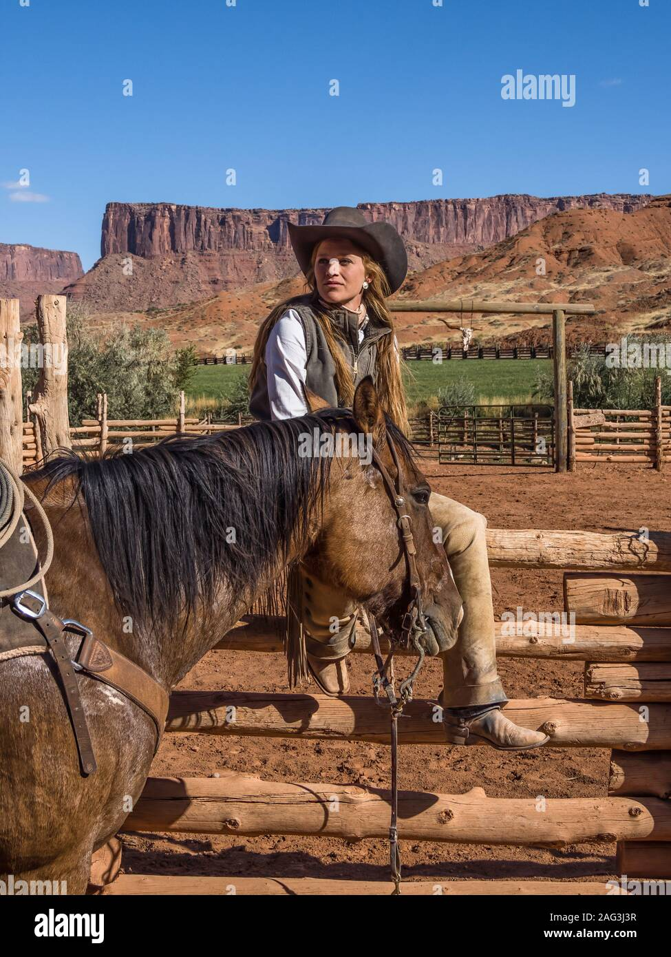 A young attractive working cowgirl wrangler sits on a wood rail fence by her horse on a ranch near Moab, Utah. Stock Photo