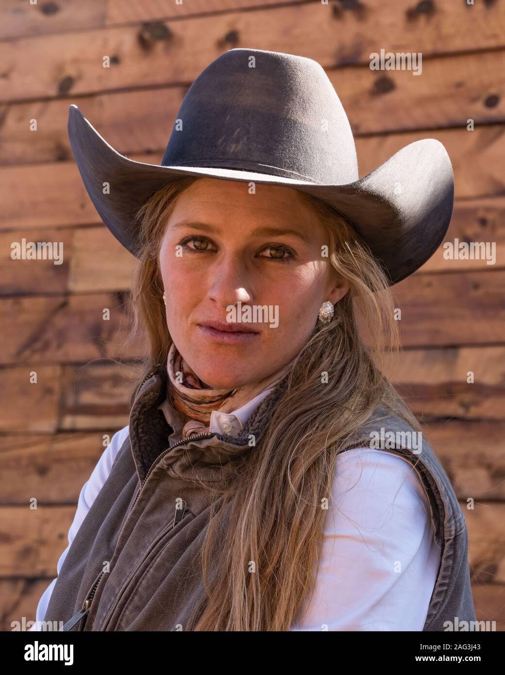 A young attractive working cowgirl wrangler poses on her horse on a ranch near Moab, Utah. Stock Photo